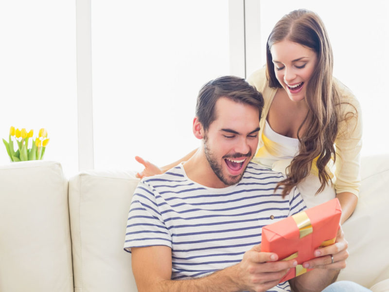 woman-surprising-her-boyfriend-with-gift-at-home-in-the-living-room